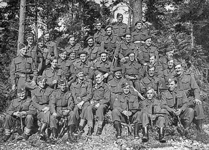 The Wimborne Group pictured at the end of the war, including the Ferndown men. Doug Gabe standing in glasses to the left, holding his Tommy gun.